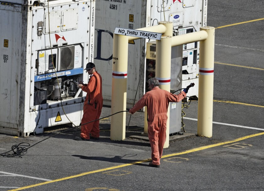 Electricians in contested jobs at the Port of Portland tend containers in 2012.