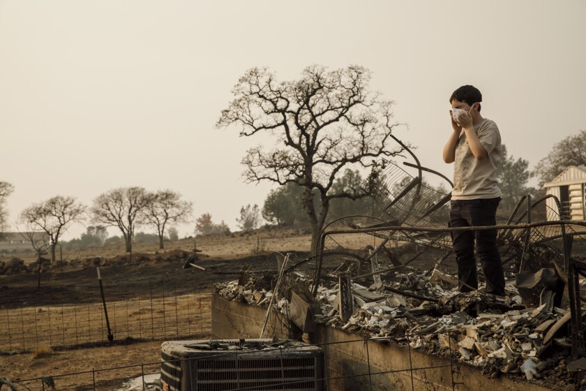 Jeremy Saylors wears a breathing mask as his family returns on Nov. 18, 2018, to the ruins of their home in Paradise, Calif., which was destroyed by the Camp fire.