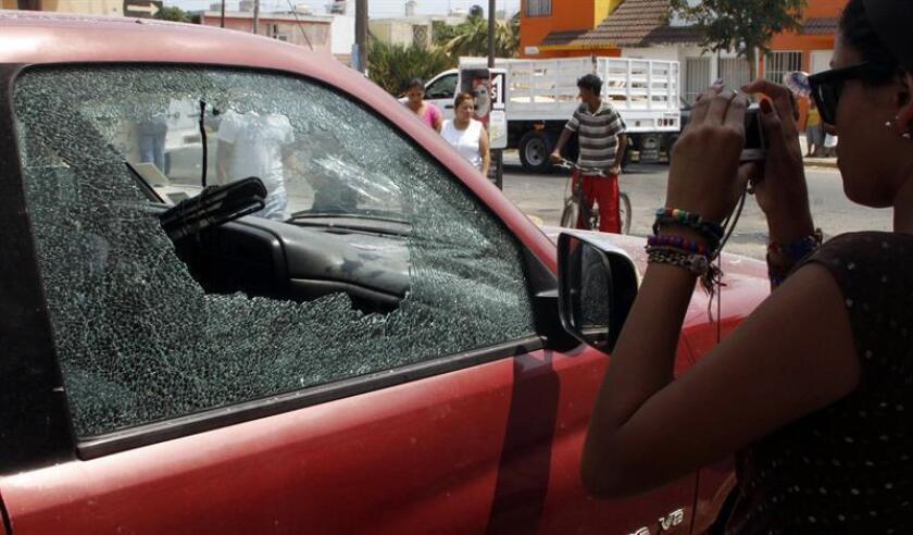 Un joven toma una fotografía el martes 19 de abril de 2011, de uno de los vehículos afectados en Veracruz, México, después de que diez presuntos narcotraficantes murieran y diez más fueran detenidos tras un enfrentamiento con soldados mexicanos, según informaron fuentes oficiales. Miembros de la Secretaría de Seguridad Pública de México y de la Fiscalía local le dijeron a Efe que los tiroteos iniciaron poco después de la medianoche del lunes en un barrio de la periferia de Veracruz, un popular destino turístico al que ya empezaron a llegar miles de visitantes por las vacaciones de Semana Santa. EFE/Archivo