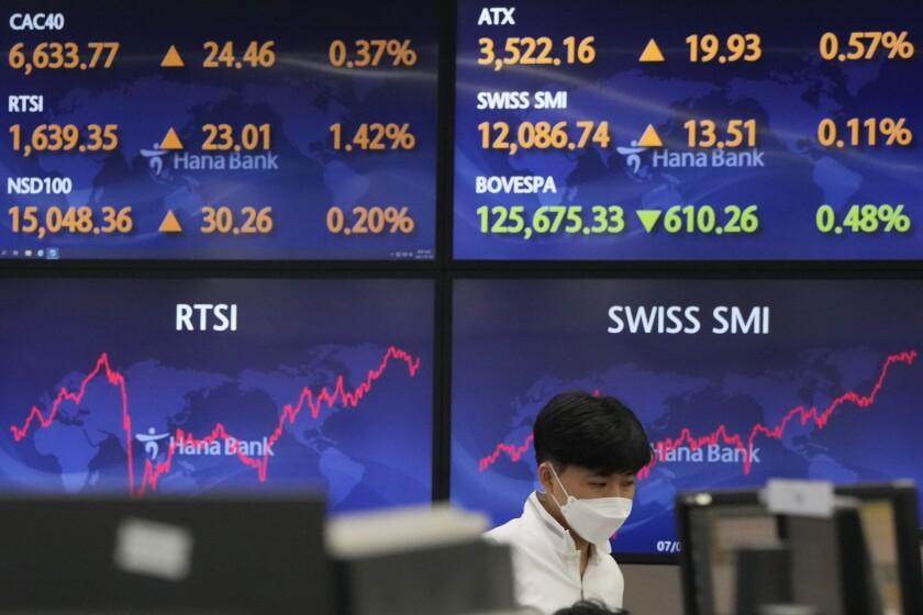 A currency trader watches monitors at the foreign exchange dealing room of the KEB Hana Bank headquarters in Seoul, South Korea, Friday, July 30, 2021. Asian shares were mostly lower Friday after stocks pushed broadly higher on Wall Street following the release of data showing the U.S. economy expanded at a 6.5% annual pace in April-June. (AP Photo/Ahn Young-joon)