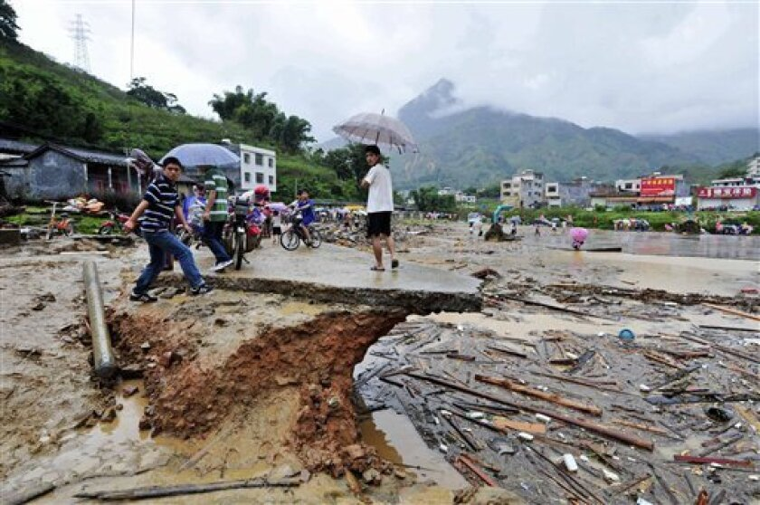 In this photo released by China's Xinhua News Agency, youth inspect destroyed roads in Qianpai Town in Xinyi, south China's Guangdong Province, Wednesday, Sept. 22, 2010. Typhoon Fanapi swamped Guangdong province after making a direct hit on the island of Taiwan on Sunday. (AP Photo/Xinhua, Chen Ye