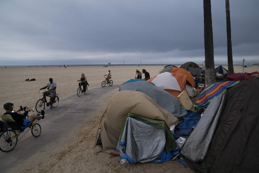 People ride their bikes past a homeless encampment set up along the boardwalk in the Venice neighborhood of Los Angeles, Tuesday, June 29, 2021. The proliferation of homeless encampments on Venice Beach has sparked an outcry from residents and created a political spat among Los Angeles leaders. (AP Photo/Jae C. Hong)