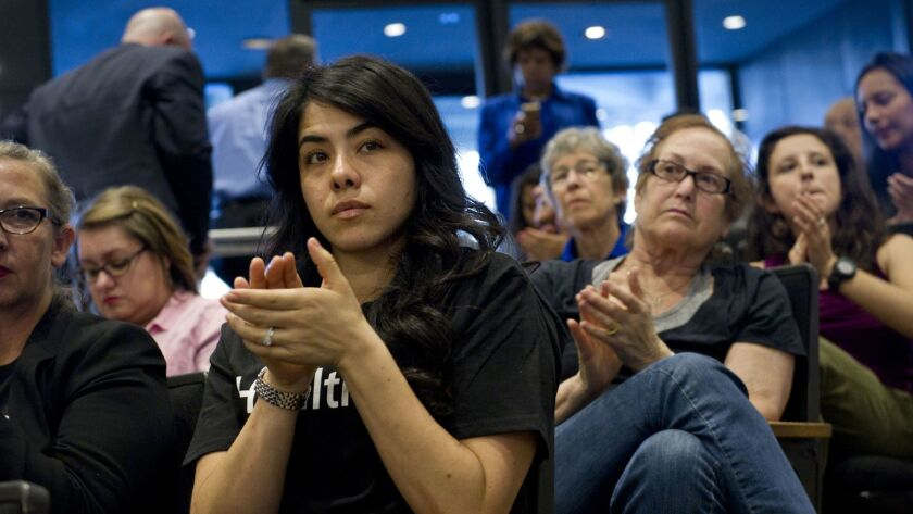 Andrea Vega Torres applauds at a workshop held by the Sacramento County supervisors to consider ways to restore healthcare assistance to undocumented immigrants. Several state proposals would extend full Medi-Cal coverage to income-eligible adult immigrants without legal status.