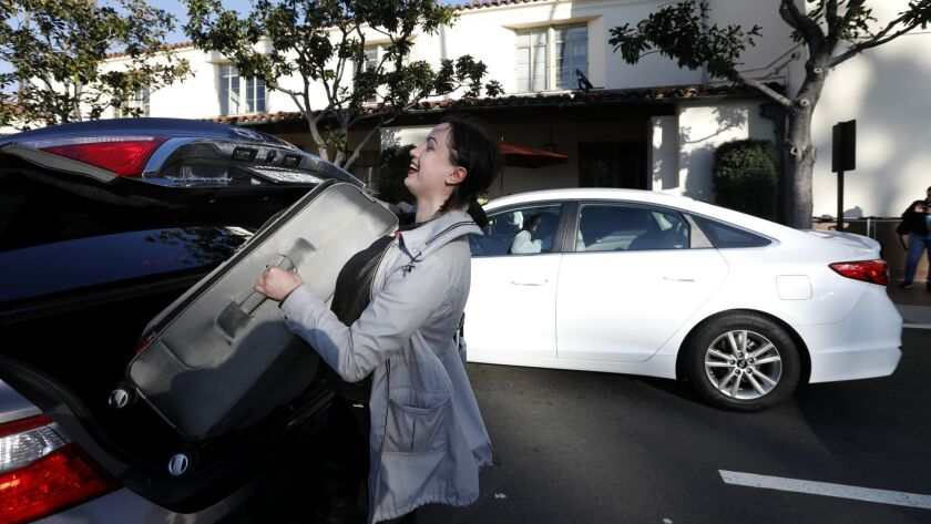 LOS ANGELES, CA February 25, 2019: Elena Markusic lifts her heavy luggage into the trunk of an at