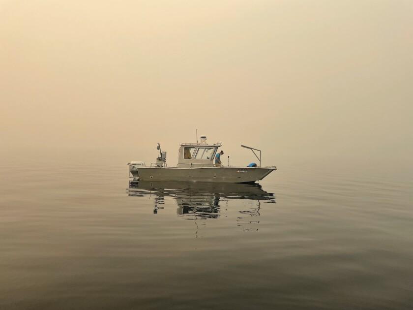 A boat floats amid a haze of smoke.
