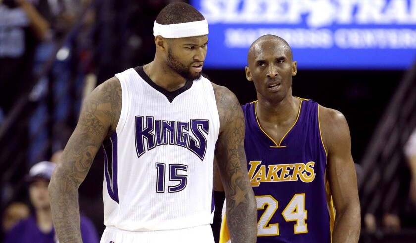 Lakers guard Kobe Bryant (24) glares at Kings center DeMarcus Cousins after getting called for an offensive foul in the fourth quarter.