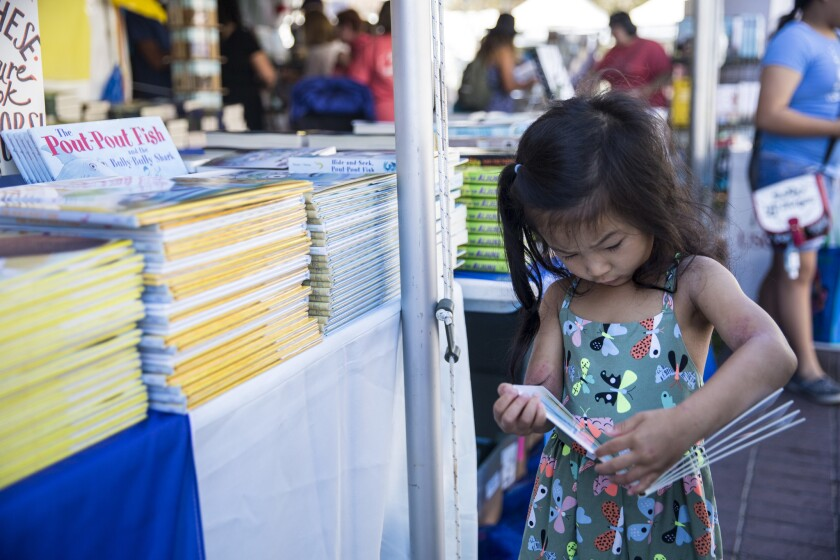 Maya Chen, 4, looks at a book during the first day of the annual Los Angeles Times Festival of Books.