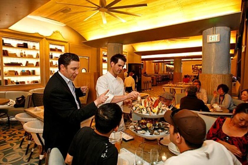 Brent Berkowitz, left, director of operations of the Innovative Dining Group, and chef Sascha Lyon show off le petit delphine -- a seafood platter -- to guests.