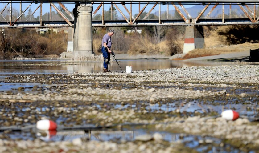 Hugh Beggs of Santa Rosa, Calif., searches for coins in the middle of the Russian River at Healdsburg Veterans Memorial Beach in Healdsburg, Calif., taking advantage of the way below normal river flow. Seventeen rural communities in drought-stricken California are in danger of running out of water