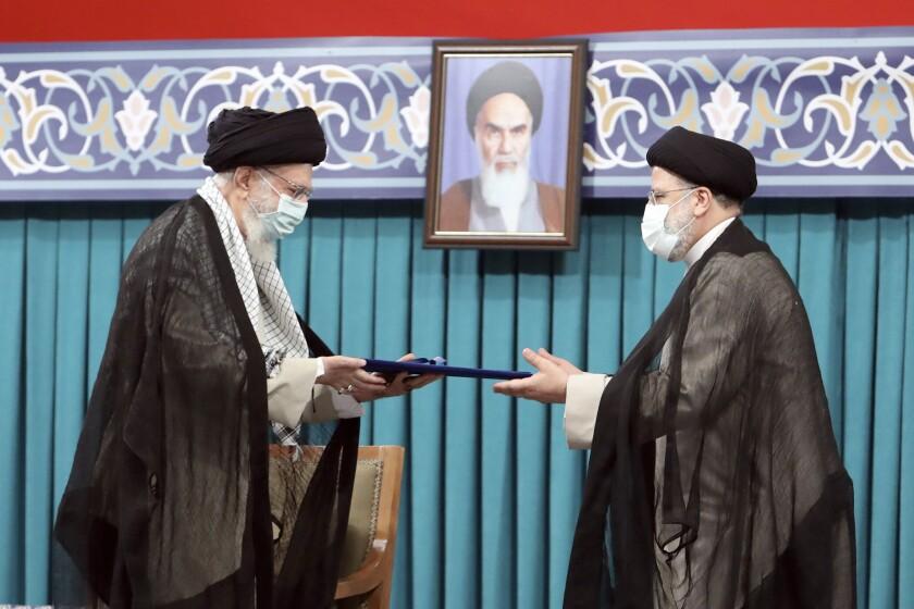 Ayatollah Ali Khamenei hands a document to Ebrahim Raisi.