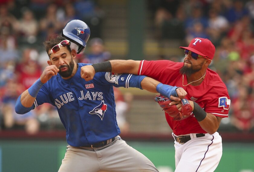 FILE - In this May 15, 2016, Toronto Blue Jays' Jose Bautista, left, is hit by Texas Rangers second baseman Rougned Odor, right, after Bautista slid into second in the eighth inning of a baseball game at Globe Life Park in Arlington, Texas. Odor's suspension for punching Bautista was reduced to sev