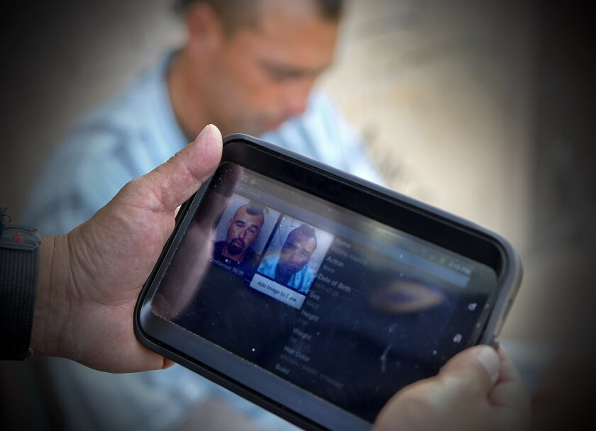 Chula Vista police Officer Roman Granados uses a computer tablet equipped with facial recognition software to photograph a person while on patrol.