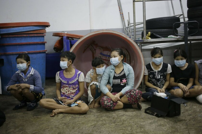 FILE - In this file photo taken Nov. 9, 2015, children and teenagers sit together to be registered by officials during a raid on a shrimp shed in Samut Sakhon, Thailand. On Tuesday a global slavery index puts India at the top of the list with the world's highest number of bonded and child laborers,