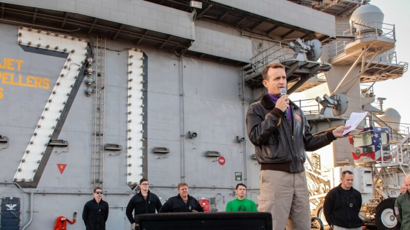 Capt. Brett Crozier, commanding officer of the aircraft carrier USS Theodore Roosevelt (CVN 71), gives remarks during an all-hands call on the ship's flight deck Dec. 15, 2019. Crozier was relieved of command Thursday after a letter he wrote asking the Navy for help with a COVID-19 outbreak was leaked to the media.