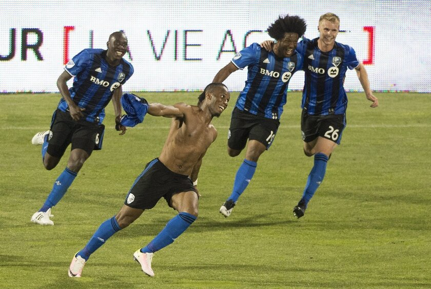Montreal Impact's Didier Drogba, foreground, celebrates with teammates Hassoun Camara (6) Michael Salazar (19) and Kyle Fisher (26) after scoring the winning goal against the Los Angeles Galaxy during second-half MLS soccer game action in Montreal, Saturday, May 28, 2016. (Graham Hughes/The Canadia