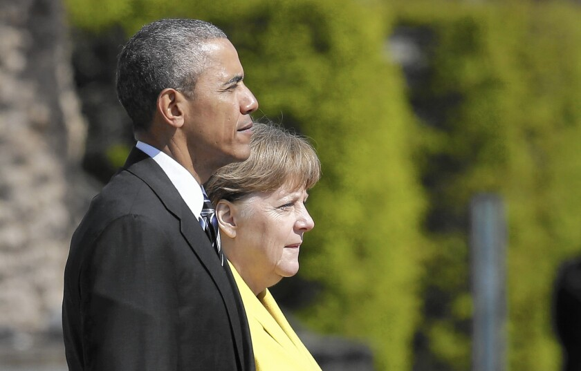 President Obama and his host, German Chancellor Angela Merkel, listen to the national anthems during a welcoming ceremony in Hanover.