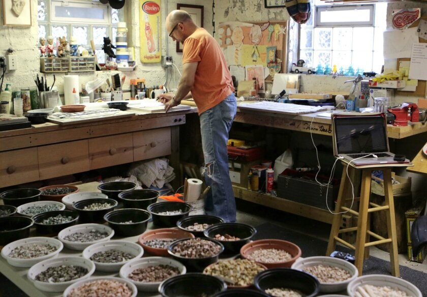 In this Monday, June 9, 2014 photo, Chicago mosaic artist Jim Bachor, looks over a checklist in his basement to make sure he has all the material he needs to complete a pothole art project. Bachor has filled a few potholes around the city and marks each one with a mosaic piece. (AP Photo/Stacy Thacker)