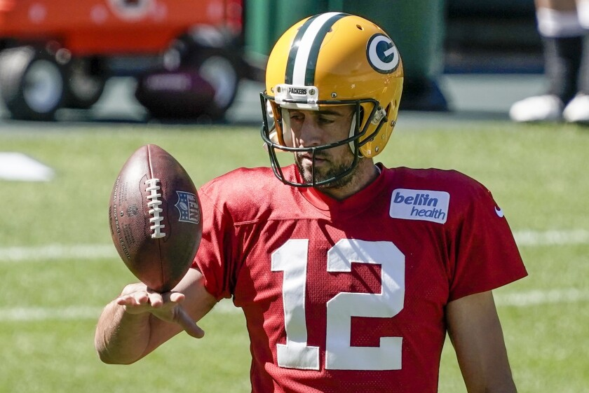 Green Bay Packers' Aaron Rodgers plays with a football during NFL football practice.