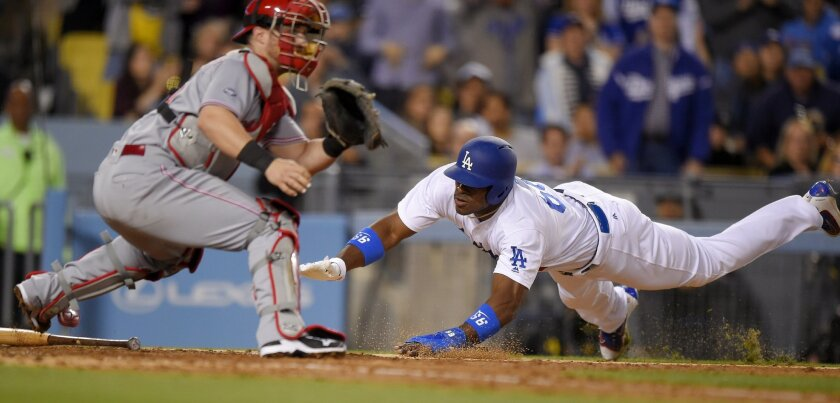 Los Angeles Dodgers' Yasiel Puig, right, scores as Cincinnati Reds catcher Tucker Barnhart waits for the throw after Howie Kendrick made it to first on an error by Reds first baseman Joey Votto during the sixth inning of a baseball game, Tuesday, May 24, 2016, in Los Angeles. (AP Photo/Mark J. Terrill)