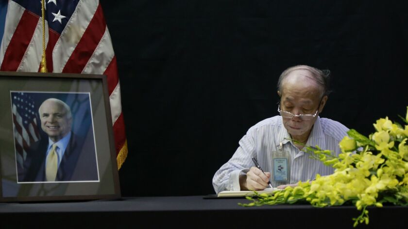 Pham Minh Chuc, an 81-year-old retiree, writes in a book of condolences for Sen. John McCain at the U.S. Embassy in Hanoi on Monday.