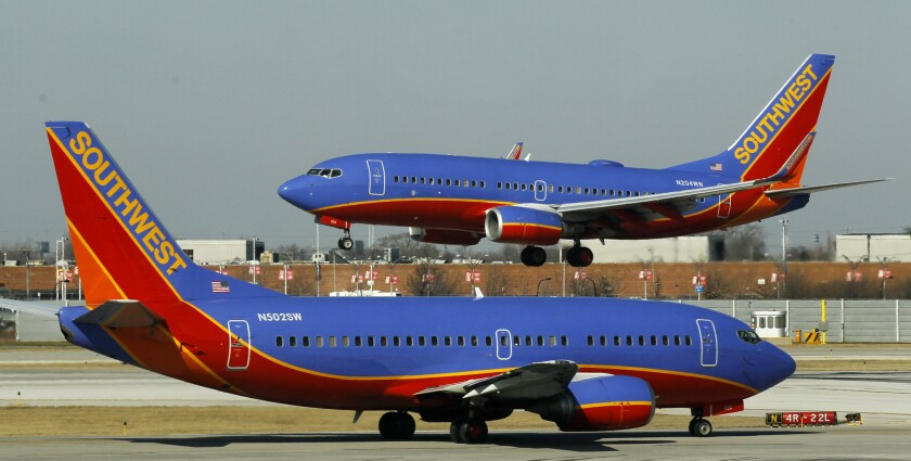 A Southwest Airlines Boeing 737 waits to take off at Chicago's Midway International Airport as another lands. Southwest Airlines has agreed to pay a $1.6-million fine for stranding passengers on delayed flights at Midway on Jan. 1 and 2, 2014.