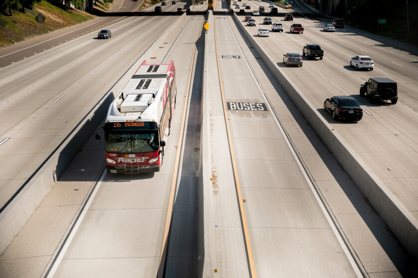 A Metropolitan Transit System bus drives along Interstate 15 on Friday, Aug. 14, 2020 in San Diego, CA.