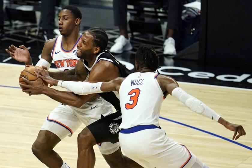 Clippers forward Kawhi Leonard tries to split the defense of Knicks guard RJ Barrett, left, and center Nerlens Noel.