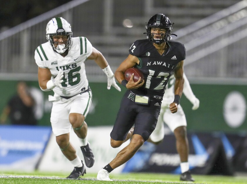 Hawaii quarterback Chevan Cordeiro (12) runs the ball as he is chased by Portland State defensive lineman Kennedy Freeman (46) during the first half of an NCAA college football game, Saturday, Sept. 4, 2021, in Honolulu. (AP Photo/Darryl Oumi)