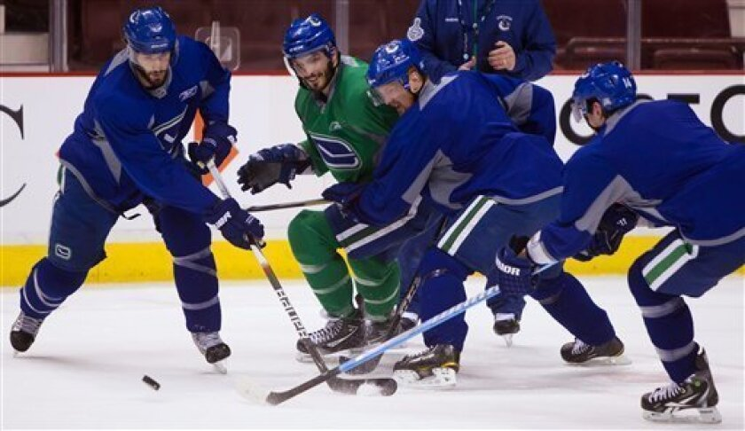 From left, Vancouver Canucks' Ryan Kesler, Aaron Rome, Henrik Sedin, of Sweden, and Alex Burrows battle for the puck during a hockey practice, Tuesday May 31, 2011, in Vancouver, British Columbia. The Canucks will face the Boston Bruins in the NHL Stanley Cup Final. (AP Photo/The Canadian Press, Darryl Dyck)