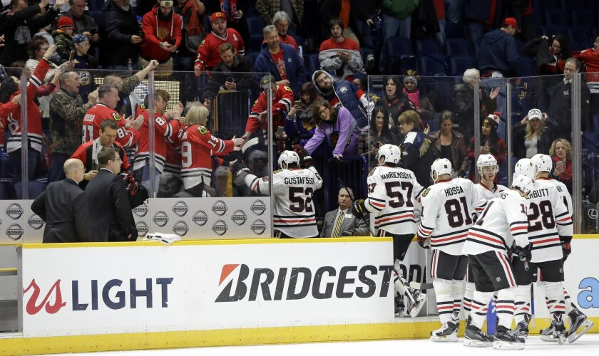 Chicago Blackhawks players are congratulated by fans as they leave the ice after defeating the Nashville Predators 4-1 in an NHL hockey game, Tuesday, Jan. 19, 2016, in Nashville, Tenn. The Blackhawks won their 12th win in a row. (AP Photo/Mark Humphrey)