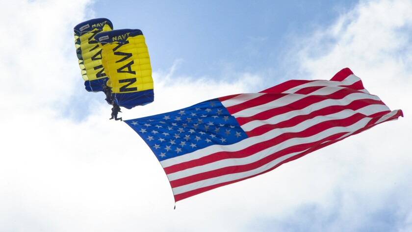 Members of the Navy precision parachute team, the Leap Frogs, fly the American flag. The team is based in San Diego.