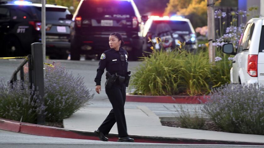 Police investigate at the scene of a shooting at the Morgan Hill Ford Store in Morgan Hill, Calif.,