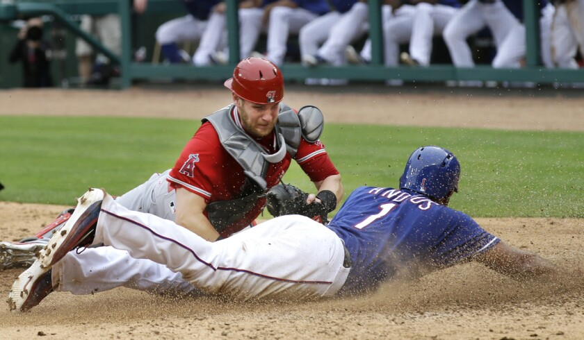 Texas Rangers Elvis Andrus, right, slides into home plate scoring against Angels catcher Jett Bandy during the sixth inning Wednesday.