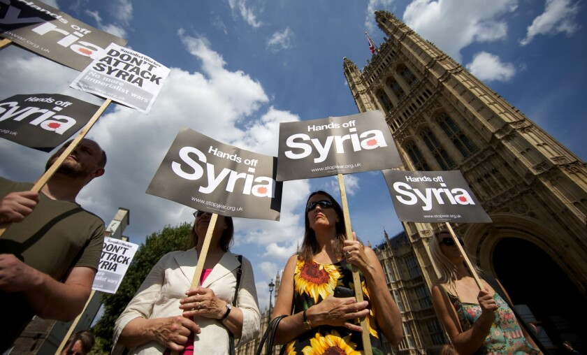 Demonstrators protest against any British military involvement in Syria outside the Houses of Parliament in London on Thursday.