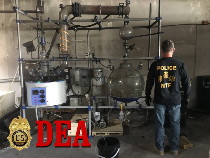 A member of the DEA's regional Narcotic Task Force looks over an El Cajon hash oil extraction lab, part of which exploded Thursday night, causing a fire in a warehouse behind a used car dealership.