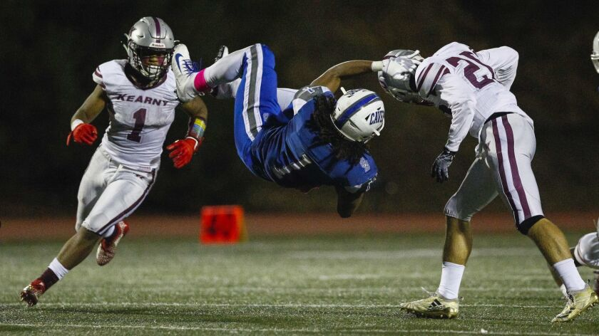 San Diego running back Raiden Hunter (1) gets rolled over as he is brought down by Kearny linebacker Shakir Swenson (23) in the second quarter.