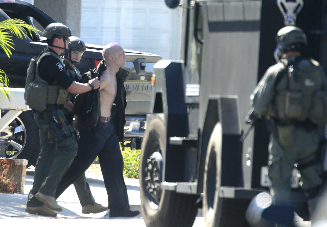 """After they fired a flash-bang grenade into the Mission Viejo home, Orange County Sheriff SWAT team members arrest Jason """"Mayhem"""" Miller on Oct. 9."""