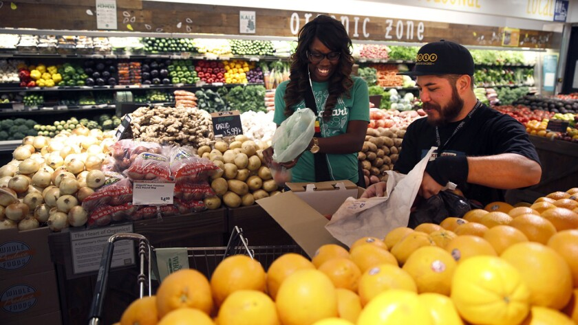Matthew Otsuka, a team member at the Whole Foods Market in Sherman Oaks, opens a box of peaches for Instacart shopper Kara Pete as she fills the online grocery order placed by Tricia Carr.