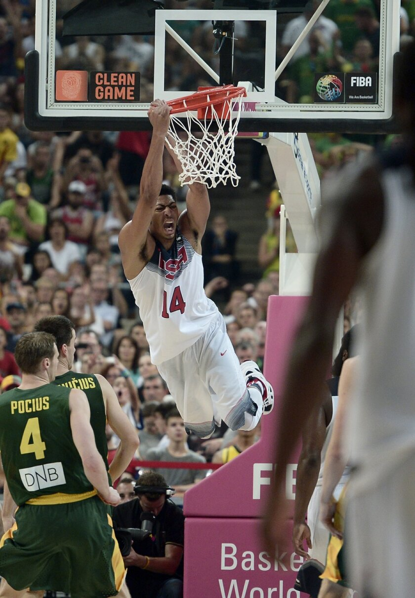 United States' Anthony Davis hangs onto the basket during the Basketball World Cup semifinal match against Lithuania at the Palau Sant Jordi in Barcelona, Spain, Thursday, Sept. 11, 2014. The 2014 Basketball World Cup competition will take place in various cities in Spain from Aug. 30 through Sept. 14. (AP Photo/Manu Fernandez)