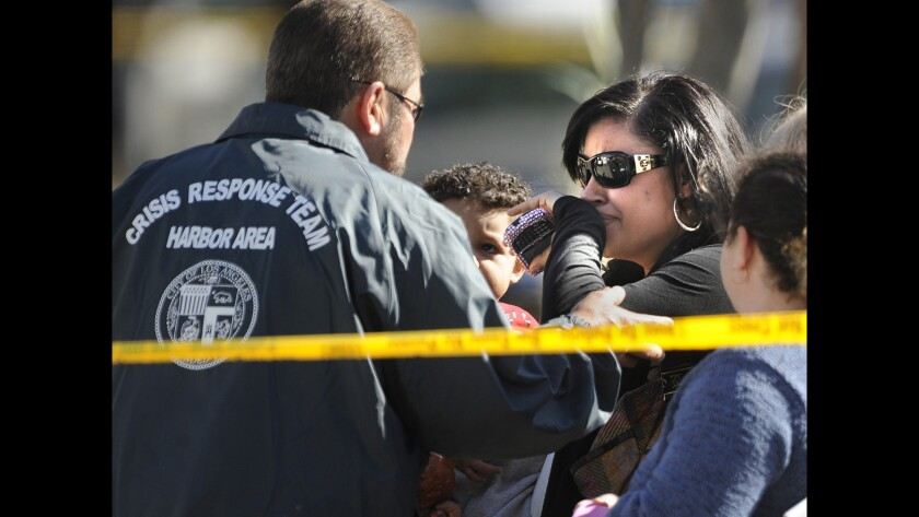 """L.A.'s Crisis Response Team helps an unidentified woman outside a home in Wilmington where seven people were found dead. The volunteer service is designed to comfort those the police usually pay the least attention to: """"surviving victims,"""" the family and friends who have to go on with their lives after disaster strikes."""