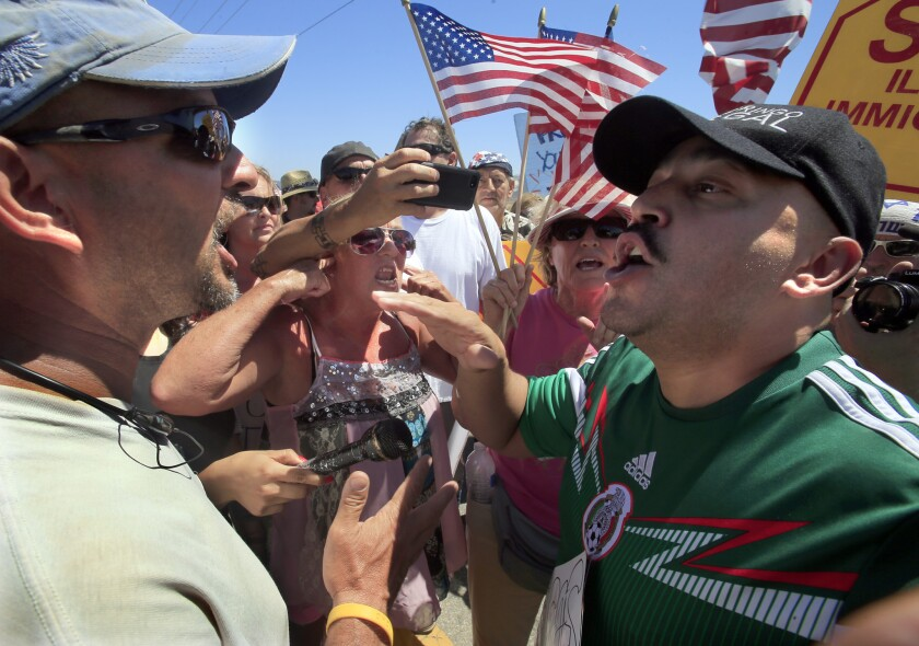A pro-immigrant rights activist squares off with a large crowd of local citizens carrying flags and posters on the street in front of the U.S. Border Patrol in Murrieta, Calif. in 2014.