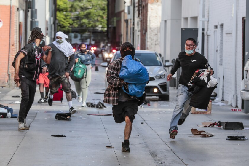 Looters rush away from police after picking through a store in downtown Santa Monica on Sunday.