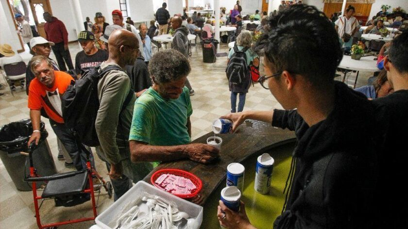 Mater Dei Catholic High School senior Jingnan Zhang, 18, pours sugar and creamer into coffee for people, many of them homeless, during the 35th birthday celebration for the Ladle Fellowship at the First Presbyterian Church.