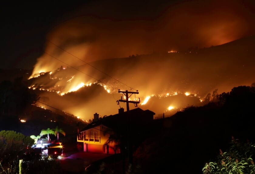 Flames were threatening homes in San Marcos Wednesday night as wildfires raged in San Diego County.