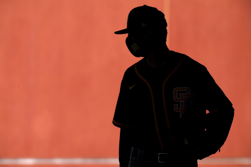 FILE - In this Saturday, Feb. 27, 2021 file photo, a player wears a face mask as he walks to a drill during San Diego Padres spring training baseball practice in Peoria, Ariz. A study published on Thursday, March 4, 2021 in JAMA Cardiology, suggests that heart inflammation is uncommon in pro athletes who've had mild COVID-19 and most don't need to be sidelined. (AP Photo/Charlie Riedel)