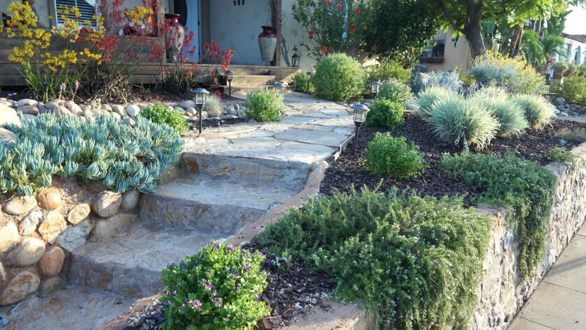 Work on the new front yard included installing a flagstone walk and modifying a rock retaining wall.
