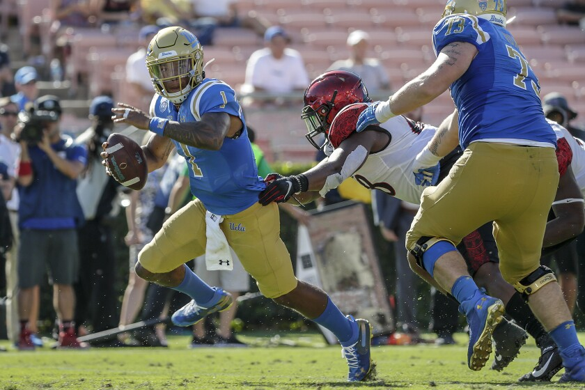UCLA quarterback Dorian Thompson-Robinson runs away from the pressure by San Diego State defensive end Myles Cheatum on Saturday at the Rose Bowl.