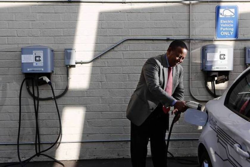 """As of July 20, there were 7,849 public and private non-residential charging stations in the United States, 1,579 of which were in California, according to the U.S. Department of Energy. Above, Yesewlik """"Leo"""" Ayalew, finance chief of clean transportation consulting firm Calstart, plugs his electric car into a charging station at his office in Pasadena last week."""