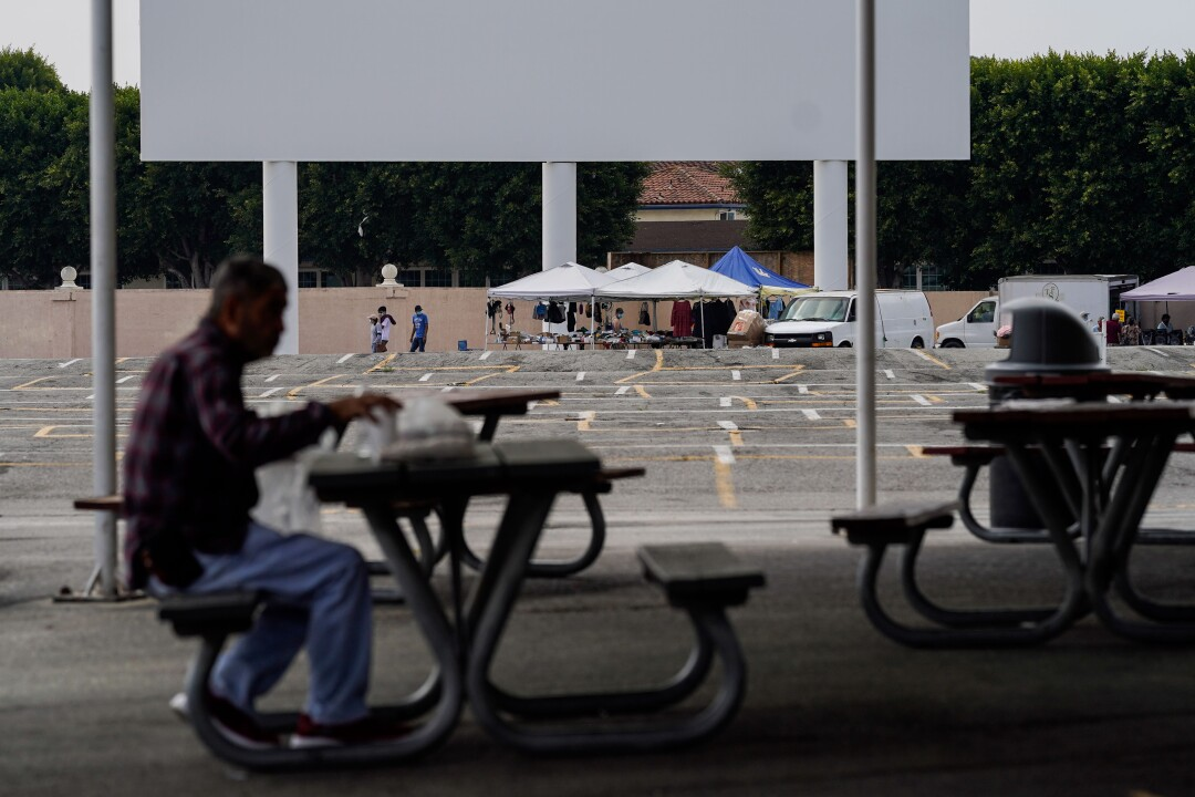 A lone vendor is seen near the drive-in movie screen at the Paramount Swap Meet, normally packed with vendors and shoppers.