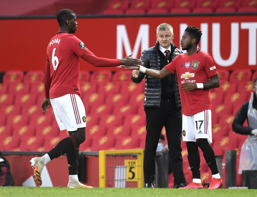 Manchester United's Paul Pogba, left, gestures to teammate Fred as he is substituted during the English Premier League soccer match between Manchester United and Southampton at Old Trafford in Manchester, England, Monday, July 13, 2020. (AP Photo/Dave Thompson,Pool)